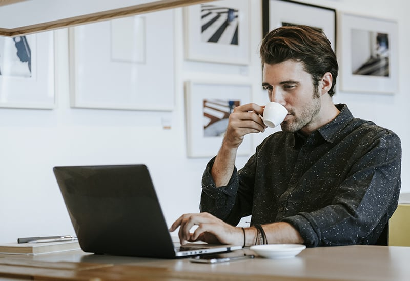 Man sipping a coffee while working