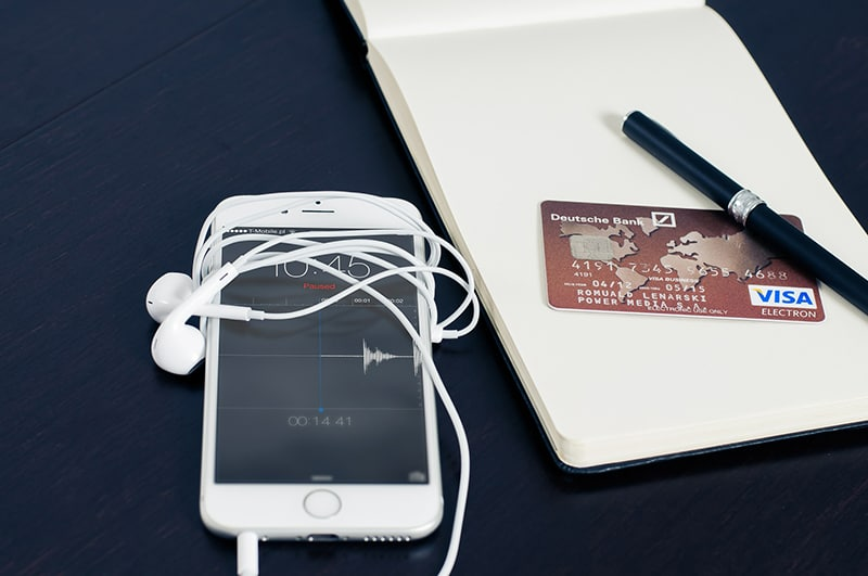 Mobile phone next to a credit card on a note pad