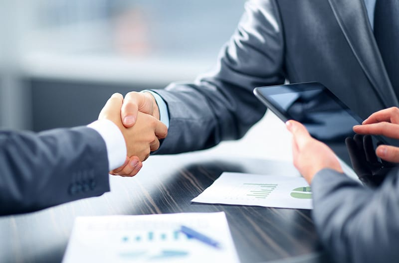 Two person wearing business suits doing the handshake