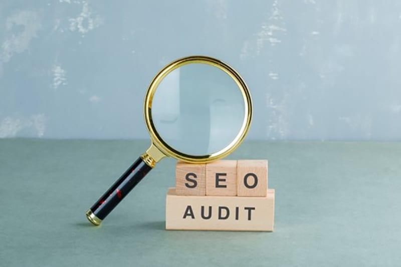 An image of SEO audit with a magnifying glass