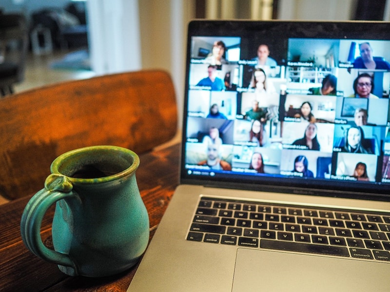 Mug next to an open laptop showing online call with multiple people