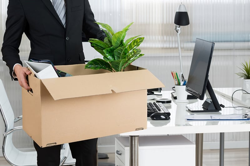 Person in black suit carrying cartoon box