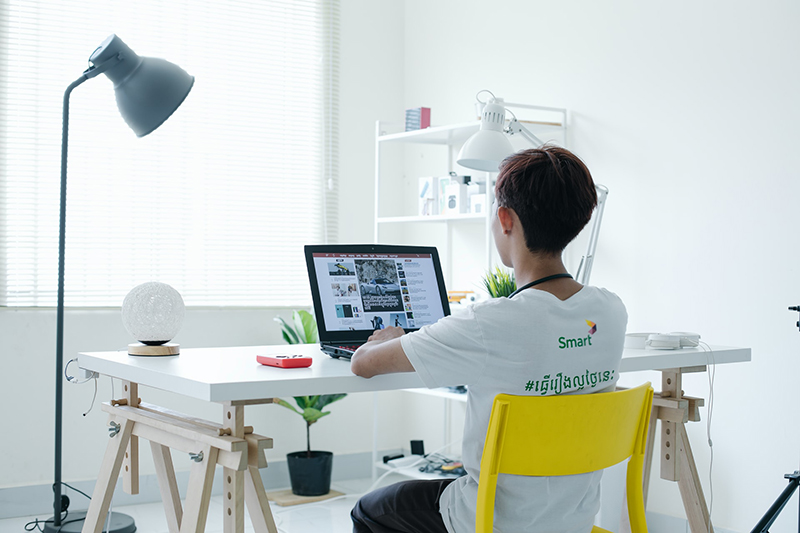 A young person sitting in front of laptop on white table