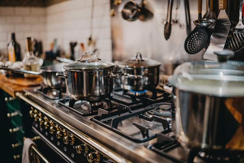 Kitchen equipment in restaurant – close-up shot of pots and pans on cooker
