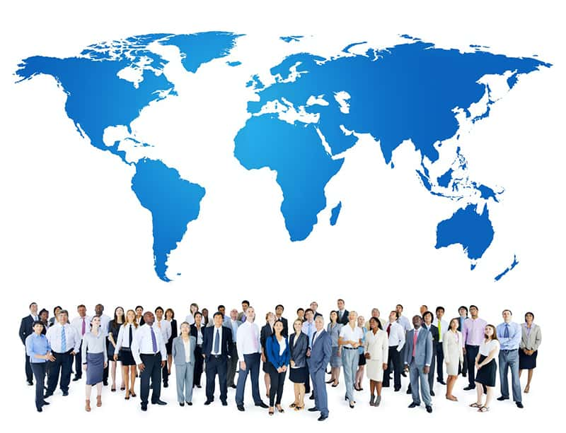 Group of employees under world map – representing global international business.