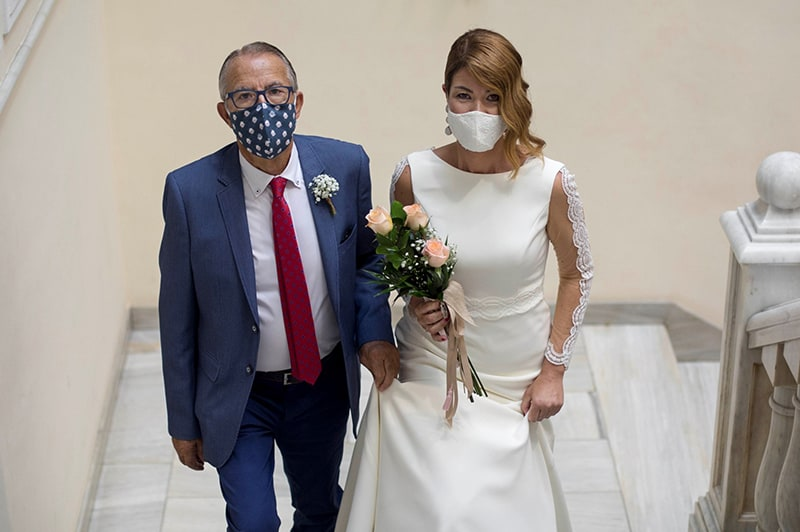Bride and father walking up stairs for wedding ceremony - both wearing masks