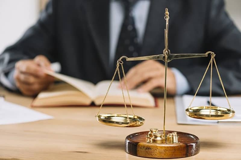 Lawyer reading a book at a desk - scales of justice on table