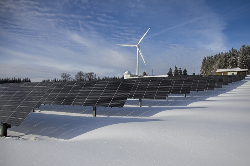 solar panels on snow with windmill