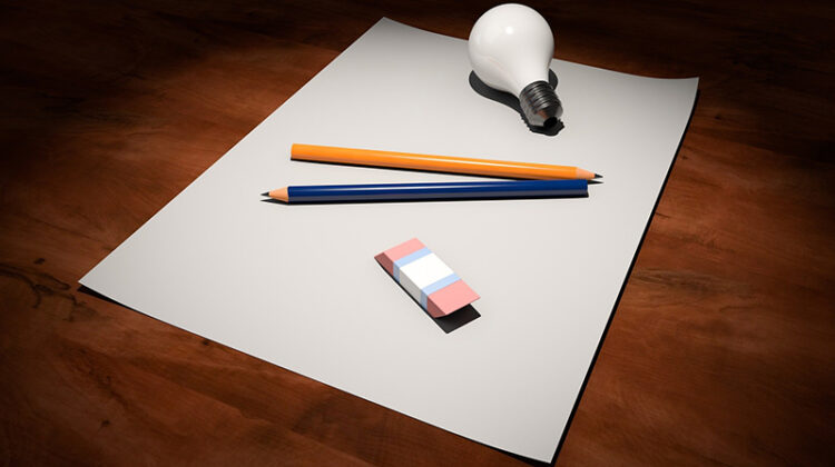 White bod paper, pencil and bulb on the top of wooden table
