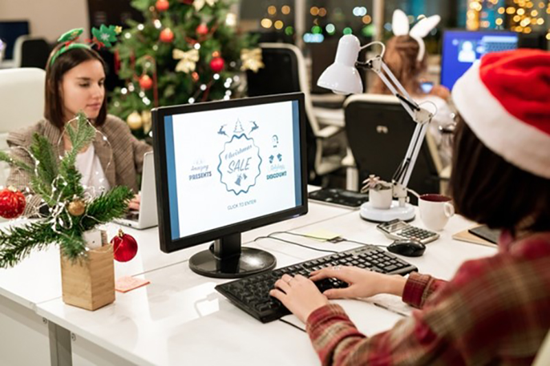 Two young businesswomen sitting in an office decorated for Christmas