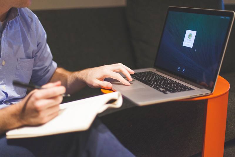 entrepreneur using laptop and writing in notebook