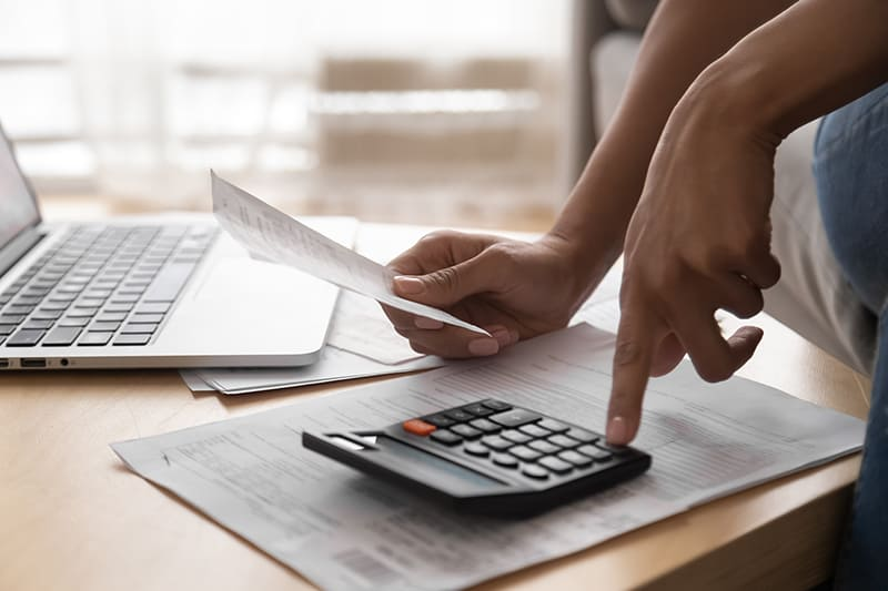 person holding a receipt and using calculator to calculate expenses