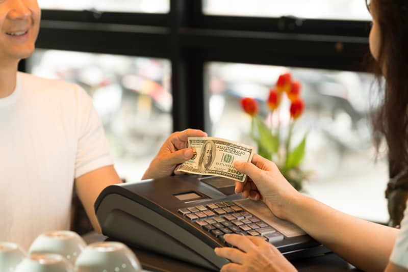 Male customer paying 100 dollar bill on the cashier