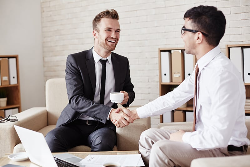 Business partners in formalwear greeting one another in office