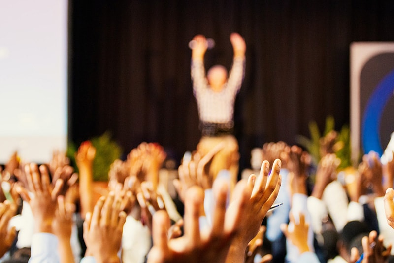 conference room full of people with their hands raised at an event