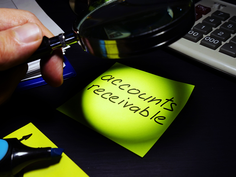 Account receivable text on green paper and a magnifying glass
