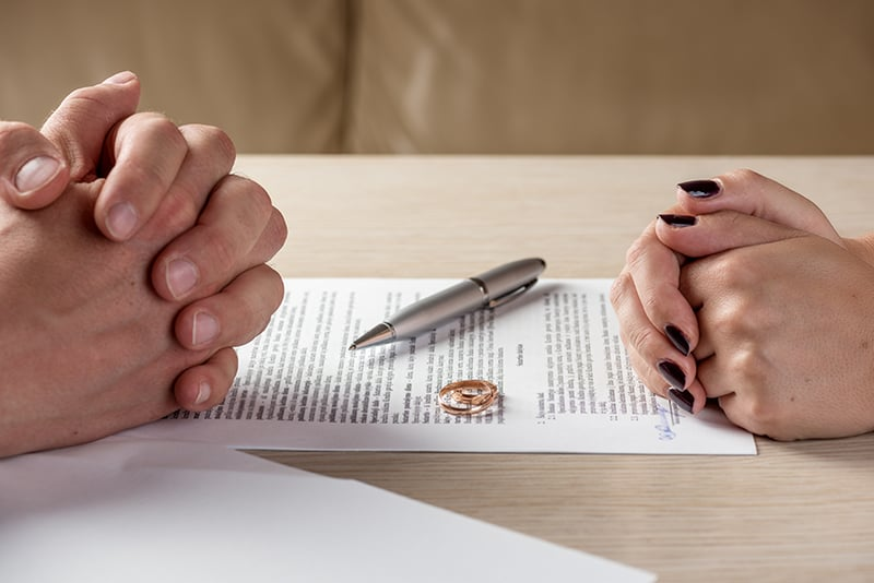 Hands of wife and husband signing divorce documents