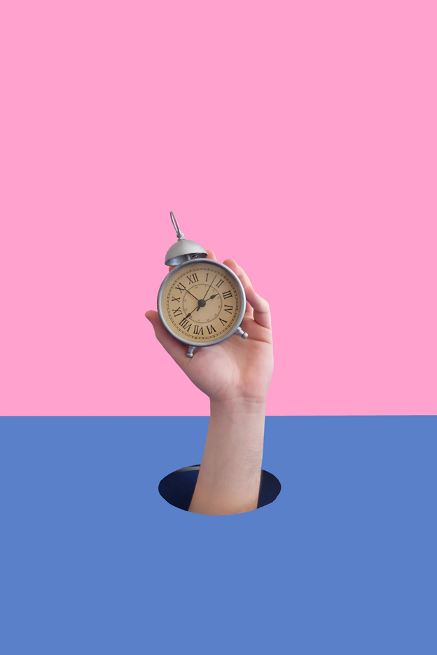 Hand holding an alarm clock – pink and blue background