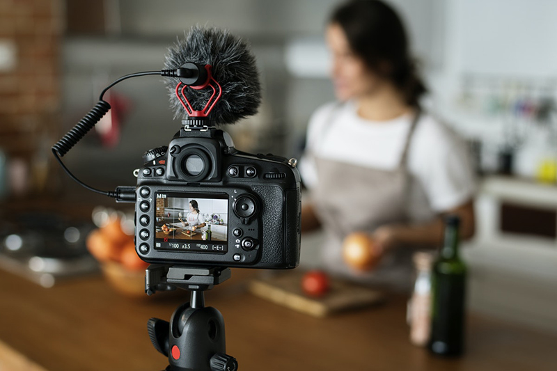 Female vlogger recording cooking related broadcast at home for video marketing