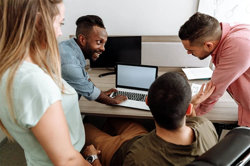 group of people having a discussion at work next to desk with computer on it