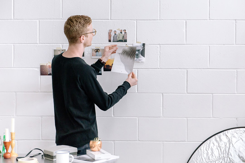 A young man attaching images on the white wall