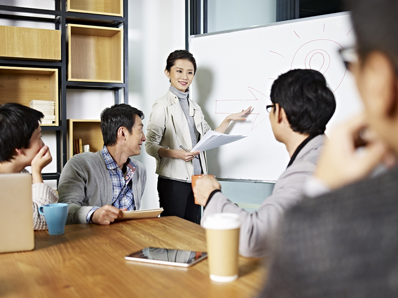 Woman standing in front near white board in the meeting