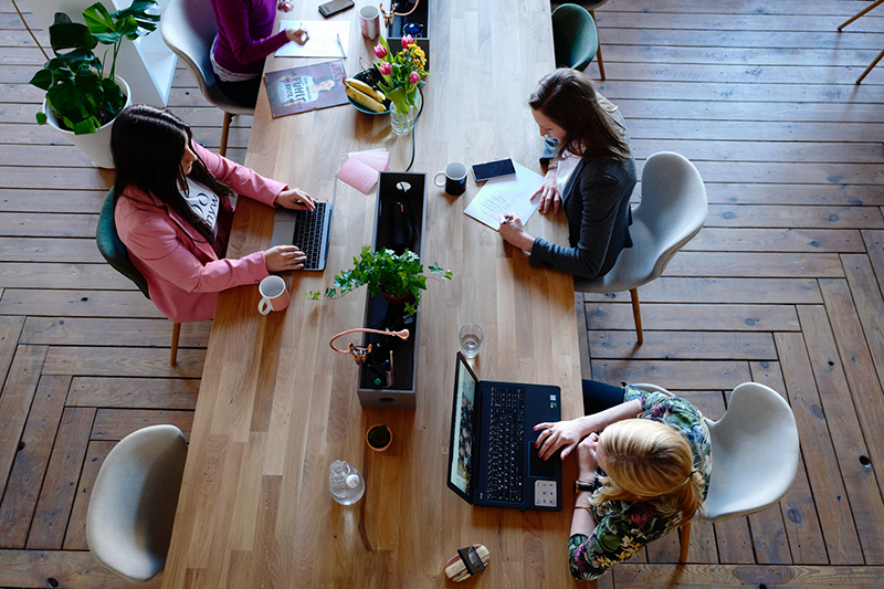 Three woman sitting on white chair on front of computer