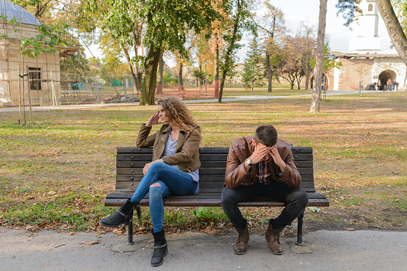 Unhappy young couple sitting on the bench