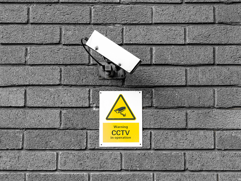 CCTV camera on grey wall with yellow sign
