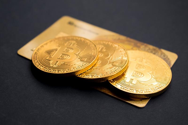 Three gold coloured bitcoin tokens on top of a gold credit card and black table
