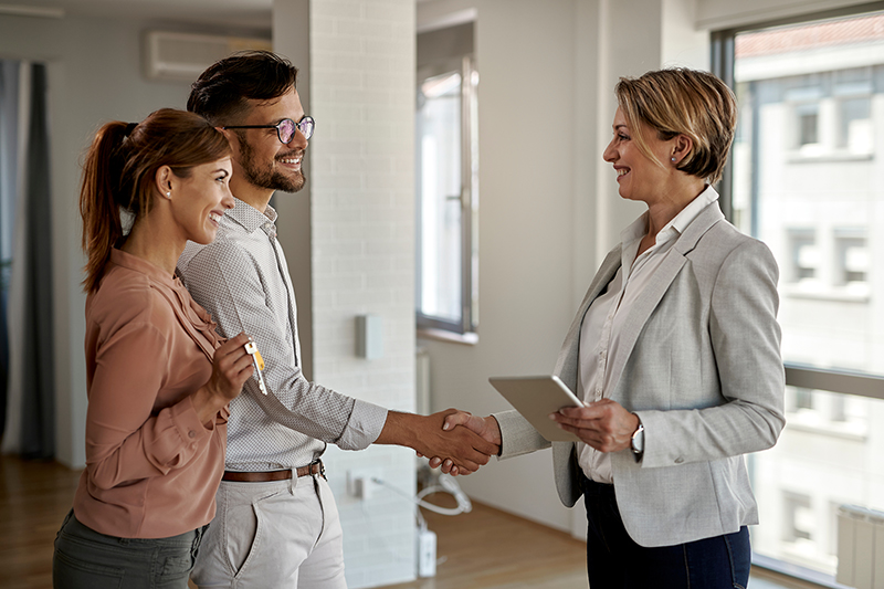 Happy real estate agent and a young couple