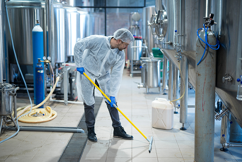 Professional industrial cleaner in protective uniform cleaning floor of food processing plant. Cleaning services and cleaning equipment.