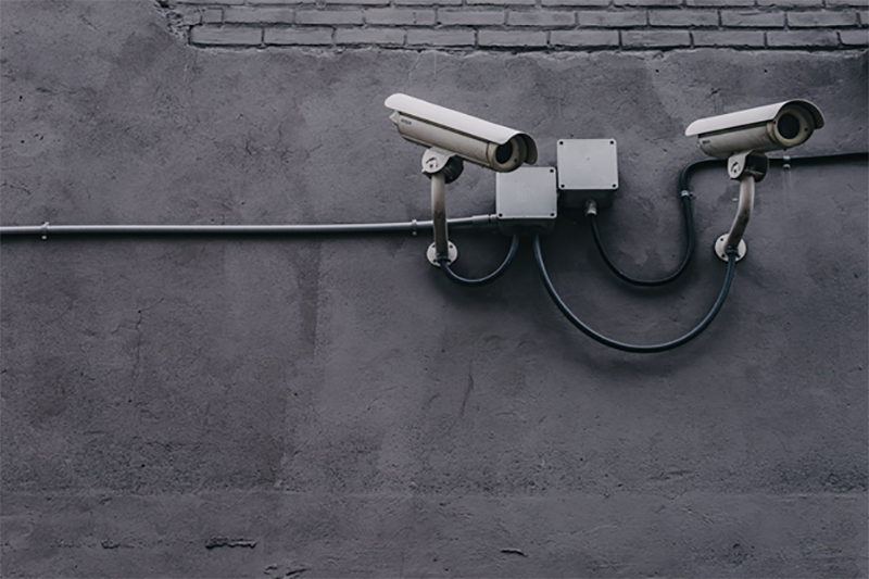 two grey securoty cameras mounted to a wall