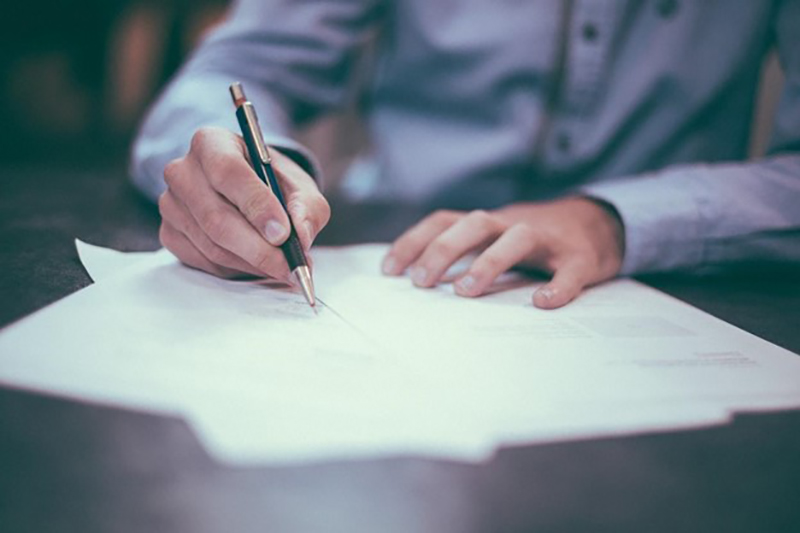 A man signing a documents on the table