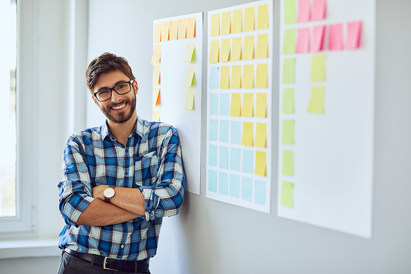Start-up businessman leaning against wall with sticky notes