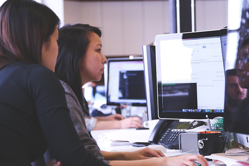 Two women working in front of computer