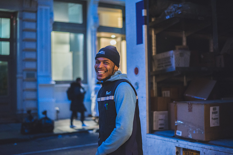 smiling man – courier next to delivery van full of parcels
