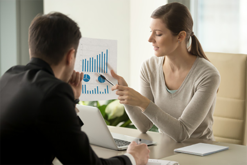 financial planner showing a client charts on a sheet of paper