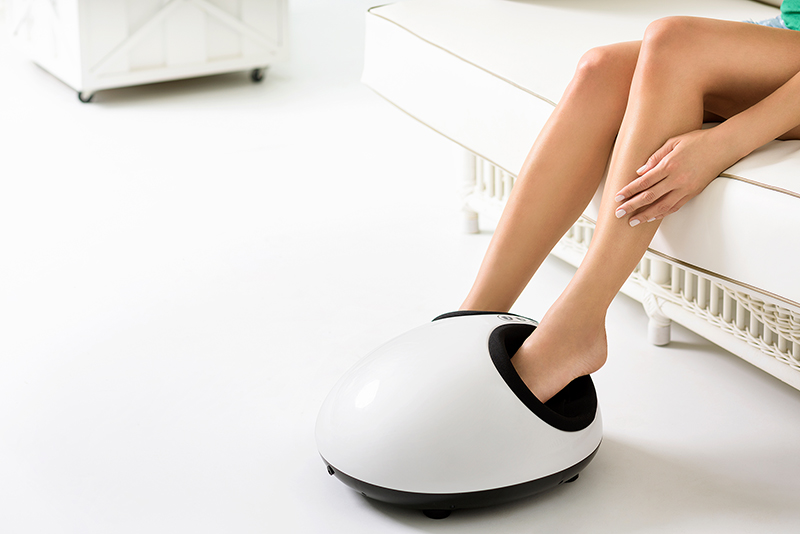 A woman relaxing while having a foot massage on a machine at home