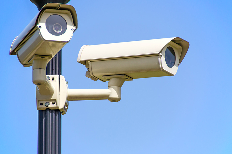 Two white Cctv camera mounted on black post