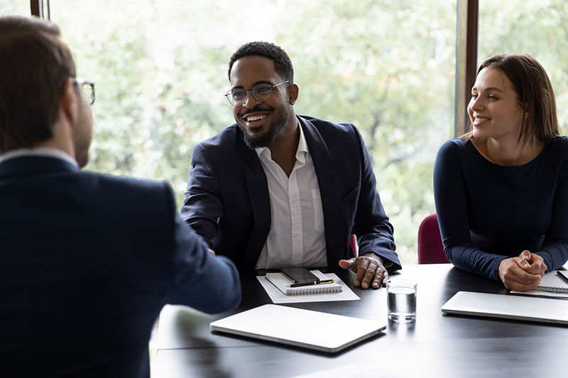 African confident executive manager welcoming client start negotiations in office. Three multiracial partners closing deal shake hands express acknowledgement and trust to future collaboration concept