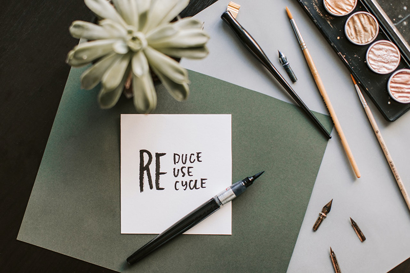 pen next to paper with words reduce reuse recycle