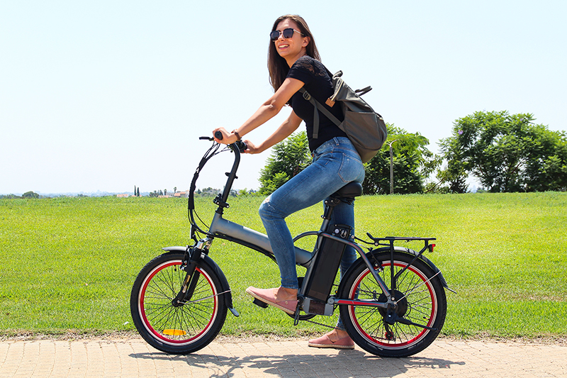 A smiling woman with electric bicycle in the park – e-bike