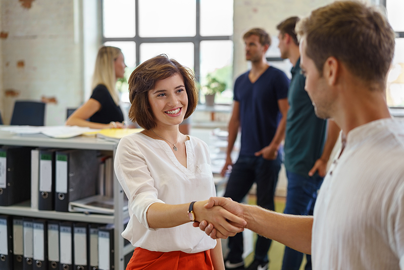 New hire - pretty young woman smiling while greeting man with handshake, standing in office environment with other people in background soft focus