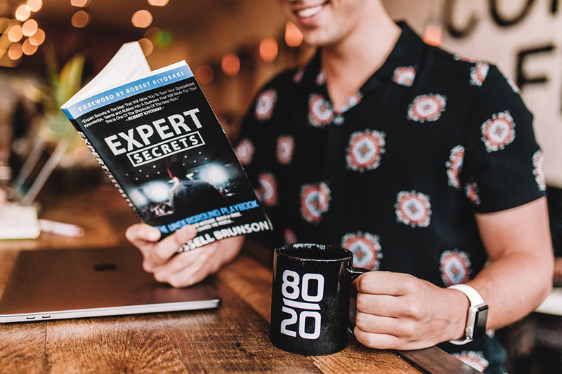 Person holding black mug while reading book of Expert secrets