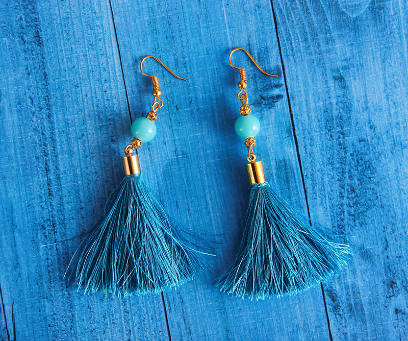 Close up photography of blue earrings