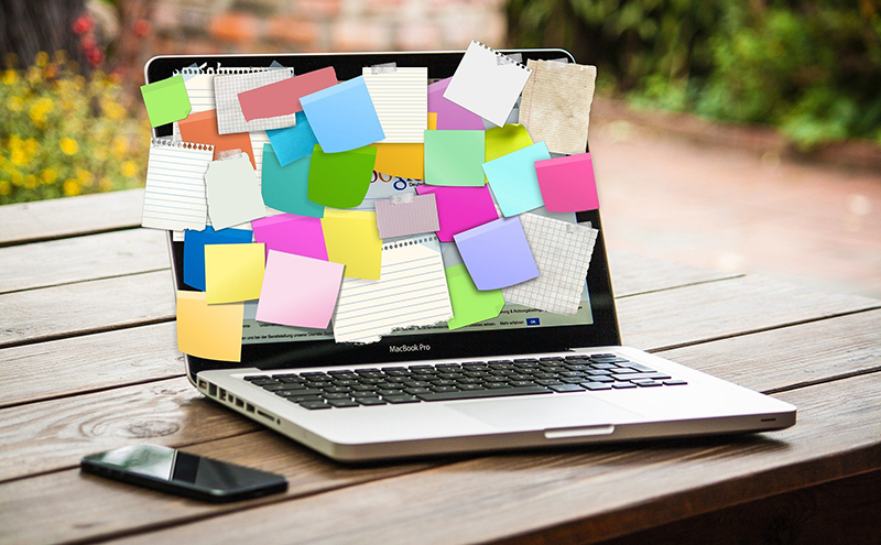 Laptop screen with sticky notes attached