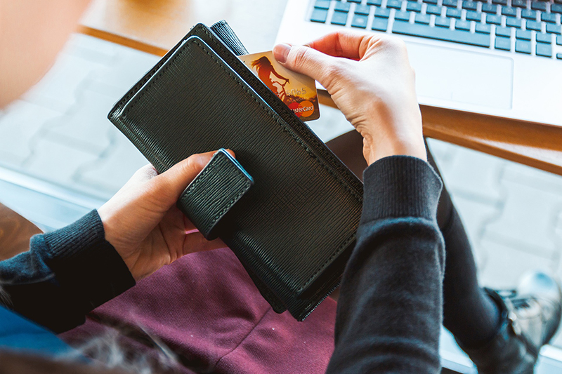 Person holding black long wallet with credit card