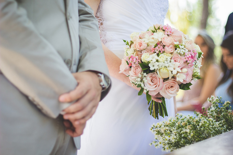 wedding couple standing in the aisle with the brode holding flowers