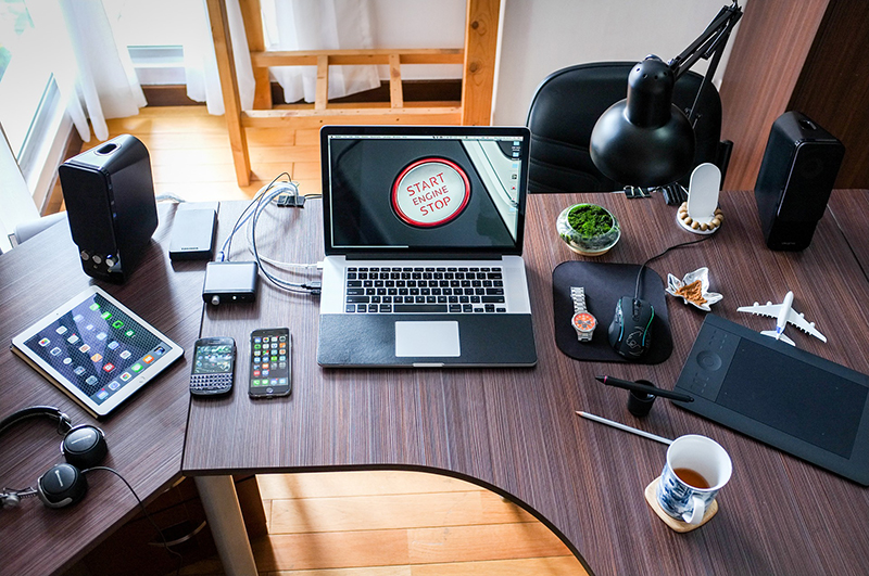 Laptop and gadgets on the top of dark brown wooden table